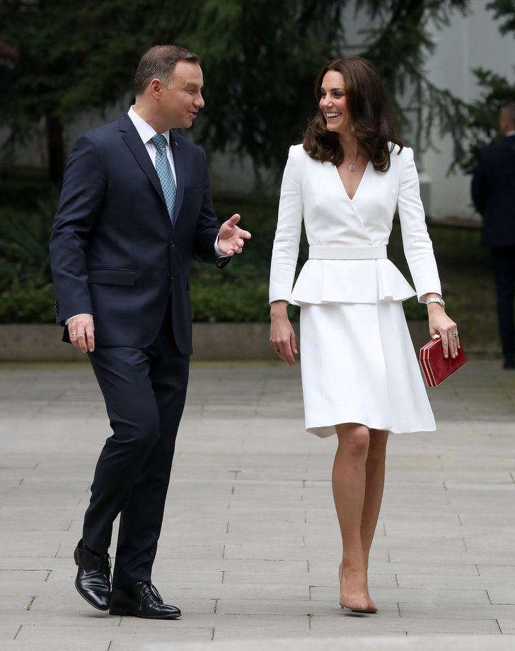 The Duchess of Cambridge arrives at the Warsaw Rising Museum in a white peplum Alexander McQueen creation, punctuated with a red clutch.  Image source Getty/Chris Jackson
